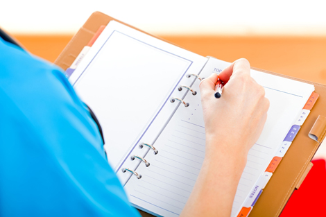 Nursing student writing notes in notebook
