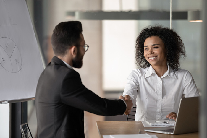 male and female shaking hands before a nursing interview