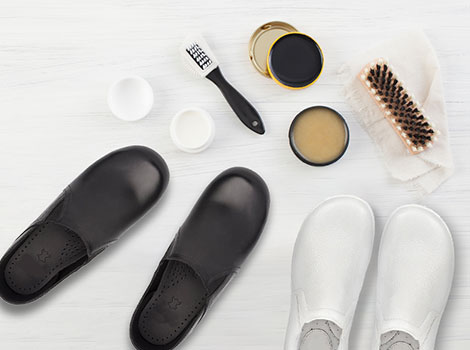 Shoes with shoe polish and brushes against a white background