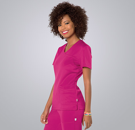 Smiling female nurse wearing pink Landau scrubs against a white background