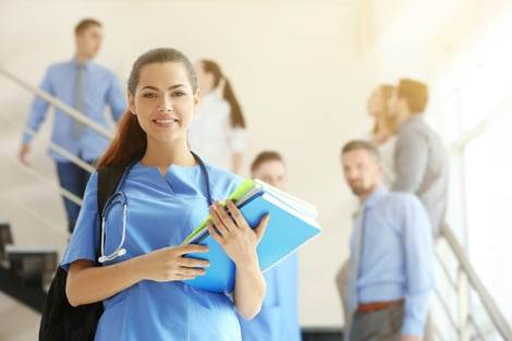 Smiling female nursing student holding a backpack and books