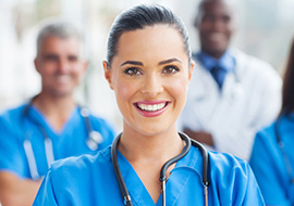smiling entry level healthcare worker standing with colleagues