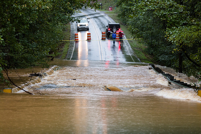 Motorists inspect a road flooded by rain from Hurricane Florence