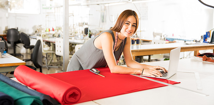 Woman on laptop with fabrics working in a textile factory