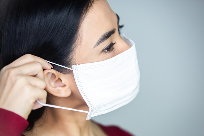 woman putting on protective face mask
