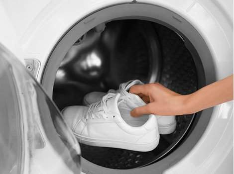 Woman putting white shoes in washing machine