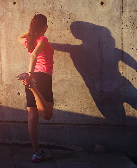 Woman standing outside stretching quadraceps muscle