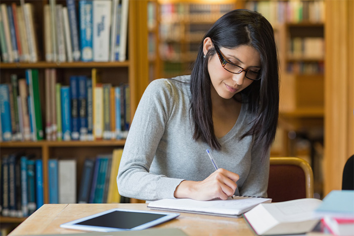 woman with textbooks studying at the library