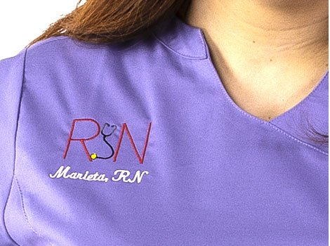 Woman wearing customized medical scrubs with emblem